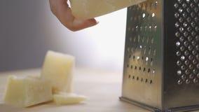 Queso parmesano italiano de la reja del cocinero con el rallador en la cocina, cámara lenta del metal almacen de video