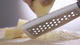 Queso parmesano italiano de la reja del cocinero con el rallador del metal en la cocina metrajes