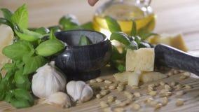 Queso parmesano, nueces de pino, sal del mar y ajo para la salsa del pesto de la albahaca que hace en la tabla de madera metrajes