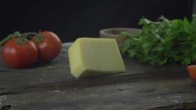 Queso parmesano que hace girar en la cámara lenta de la tabla de cocina metrajes