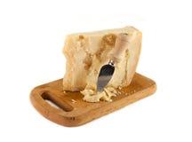 Queso parmesano y cuchillo en una tajadera Imagen de archivo libre de regalías