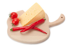 Queso, pimiento picante y tomates en un tablero de madera Foto de archivo libre de regalías