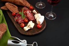 Queso, prosciutto, pan, verduras y especias en el tablero de madera en fondo negro con el espacio de la copia Imagen de archivo libre de regalías