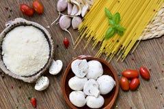 Queso rallado, ajos, setas, tomates de cereza y espaguetis Imagen de archivo