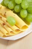 Queso rebanado y uvas verdes Fotos de archivo libres de regalías