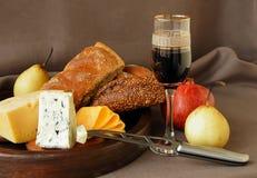 Queso, un vidrio de vino, fruta y pan. Fotos de archivo libres de regalías