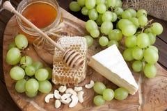 Queso, uva y miel en el tablero de madera Imágenes de archivo libres de regalías