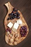 Queso, uva y miel en el tablero de madera Imagenes de archivo