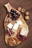 Queso, uva y miel en el tablero de madera Foto de archivo