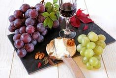 Queso, uvas, nueces y vidrio franceses de vino rojo Fotografía de archivo