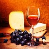 Queso, uvas y vidrio de vino rojo Foto de archivo