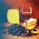 Queso, uvas y vidrio de vino rojo Fotos de archivo libres de regalías