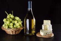 Queso verde, botella de vino y uvas Imagen de archivo libre de regalías