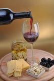 Queso y aceitunas de la botella de vino Fotos de archivo libres de regalías