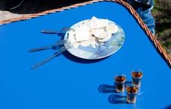 Queso y huevos hervidos en la placa con tres bifurcaciones y tres pequeños vidrios de brandy imagenes de archivo