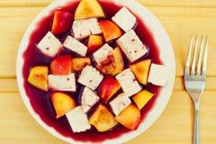 Queso y melocotones en la salsa de vino rojo, postre en la tabla de madera, entonada Imagen de archivo