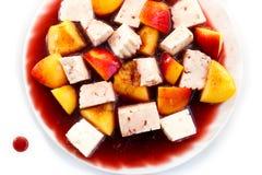 Queso y melocotones en la salsa de vino rojo, postre sabroso Fotos de archivo