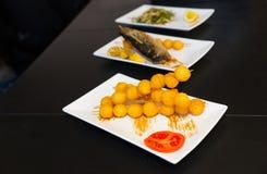 Queso y pescados fritos deliciosos en las placas blancas Fotografía de archivo