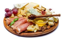 Queso y prosciutto del camembert con la miel, higos, nueces en el tablero de madera Imágenes de archivo libres de regalías