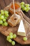 Queso y uva del camembert en fondo de madera Imagen de archivo libre de regalías