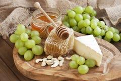 Queso y uva del camembert en fondo de madera Fotos de archivo libres de regalías