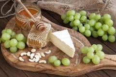 Queso y uva del camembert en fondo de madera Fotos de archivo