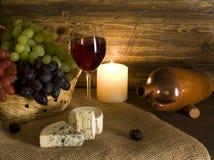 Queso y uvas con el vidrio de vino rojo Foto de archivo libre de regalías