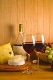 Queso y uvas con los vidrios de vino rojo Imagenes de archivo