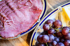 Queso y uvas en la placa Imágenes de archivo libres de regalías