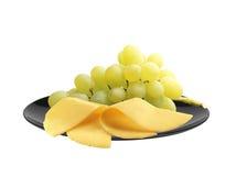 Queso y uvas maduras en la placa negra aislada en blanco Imagenes de archivo