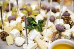 Quesos, aceitunas, nueces y uvas en un tablero de madera Foto de archivo