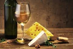Quesos con un vidrio y una botella de vino en una tabla de madera Fotografía de archivo libre de regalías