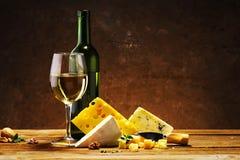 Quesos con un vidrio y una botella de vino en una tabla de madera Imagen de archivo