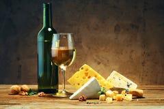 Quesos con un vidrio y una botella de vino en una tabla de madera Fotografía de archivo