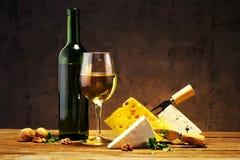 Quesos con un vidrio y una botella de vino en una tabla de madera Foto de archivo libre de regalías