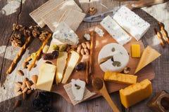 Quesos deliciosos en la tabla de madera Foto de archivo libre de regalías