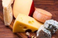 Quesos en tablero del queso Fotos de archivo