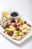 Quesos, pera, nueces y uvas clasificados en una placa Imagen de archivo