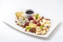 Quesos, pera, nueces y uvas clasificados en una placa Foto de archivo libre de regalías