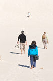 Quest. The long walk: group of four tired people slowly walking up a white sand dune, bare feet; symbol for adventurous / arduous journey or spiritual quest Stock Images
