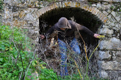 Quest for ancestorship. Hooded man obscured by overgrown plants under arched recess of rural ruin Stock Images
