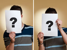 Question. Young man holding a white page with question mark in front of his face Royalty Free Stock Images