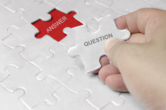 QUESTION AND ANSWER JIGSAW PUZZLE. Image of a hand holding a piece of jigsaw puzzle with question and answer words Royalty Free Stock Image