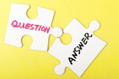 Question and answer words. Written on two pieces of jigsaw puzzle Stock Photos