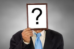 Question. Businessman holding a white billboard with a question mark on it Royalty Free Stock Photos