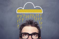 Question Cloud. Sign on the blackboard businessman looking up Stock Photos