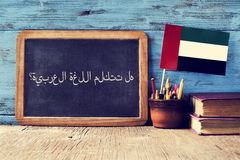 Question do you speak Arabic? written in Arabic. A chalkboard with the question do you speak Arabic? written in Arabic, a pot with pencils, some books and the Royalty Free Stock Photos