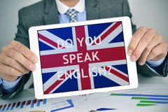 Question do you speak English? in a tablet computer. Closeup of a young caucasian businessman at his office desk full of charts showing a tablet computer with Royalty Free Stock Photography