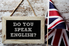 Question do you speak English?. A wooden-framed chalkboard with the question do you speak English? written in it and a flag of the United Kingdom against a Stock Photography