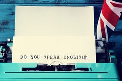Question do you speak english? written with a typewriter. Closeup of a paper in an old blue typewriter with the question do you speak english? typewritten in it Stock Image